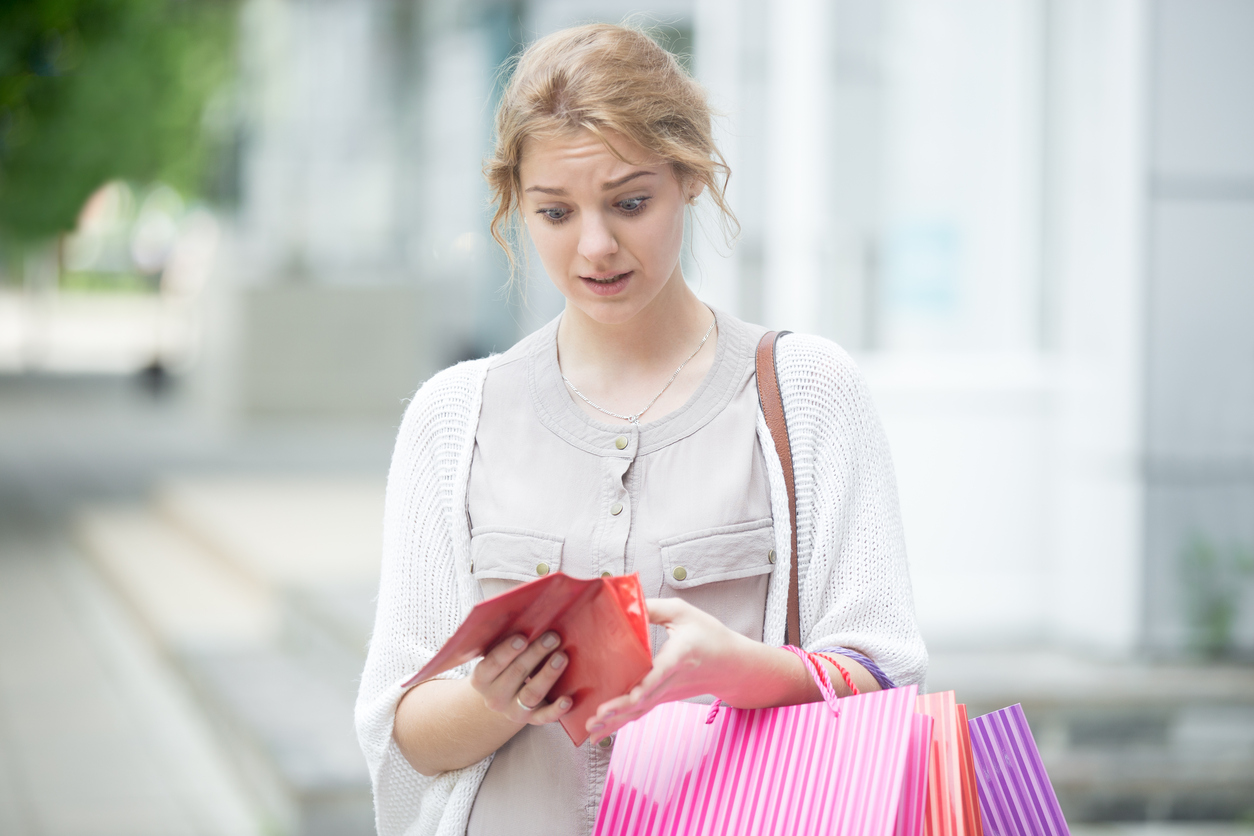 Portrait of unhappy stressed beautiful person looking in open wallet with shocked expression while holding color shopping bags at mall entrance. Young model spent too much money during shopping time