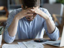 Man pondering bankruptcy paperwork